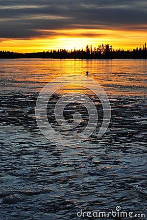 Sunset on ice lake
