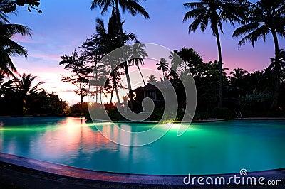 Sunset and illuminated swimming pool