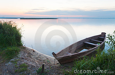Sunset with old flooding boat on summer lake shore