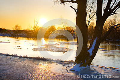 Sunset over frozen river in winter