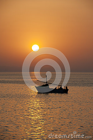 Sunset over the ocean with a boat