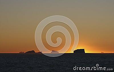 Sunset over ocean icebergs
