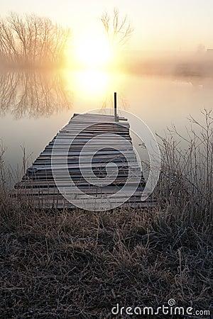 Sunset over pier on lake