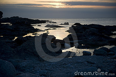 Sunset over rocky shoreline