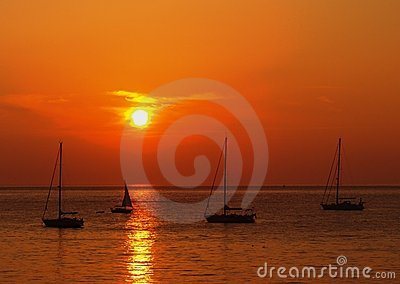 Sunset over yachts in calm sea