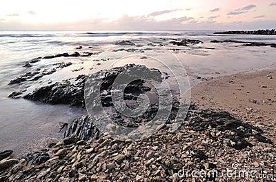 Sunset and rocky beach