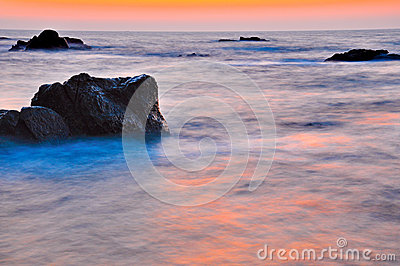 Sunset at rocky sea shore