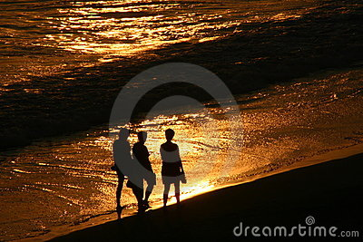 Silhouettes walking on the beach at sunset