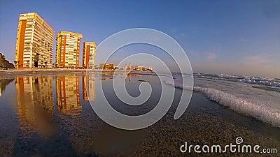 Sunsetting sur la plage avec l'éclairage d'or sur des hôtels clips vidéos