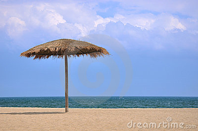 Sunshade on beach with blue sky and white cloud