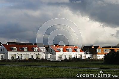 Sunshine on houses under a thunder sky