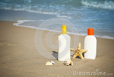 Suntan Lotion Flacons on the Beach with copy space