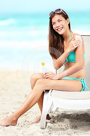 Suntan lotion - woman applying sunscreen