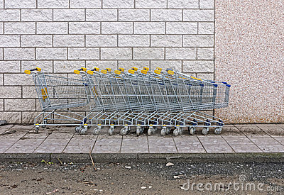 Supermarket shopping trolleys by wall