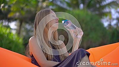 Superslowmotion disparou de uma jovem mulher em uma praia tropical senta-se em um sofá inflável e bebe-se a água de um multi filme