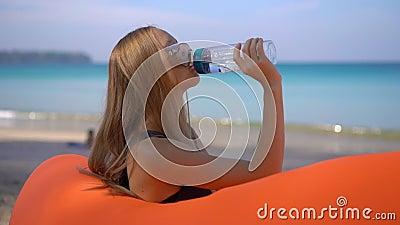 Superslowmotion disparou de uma jovem mulher em uma praia tropical senta-se em um sofá inflável e bebe-se a água de um multi vídeos de arquivo