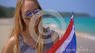 Superslowmotion disparou de uma jovem mulher que bonita vestir óculos de sol reflexivos guarda uma bandeira nacional de Tailândia filme
