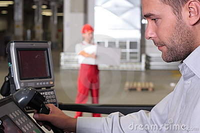 Supervisor at control panel in factory