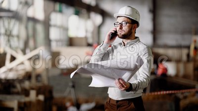 Supervisor with plan talking phone. Man in hard hat and formal clothing standing on site with plan in hands and talking. Man in hard hat and formal clothing stock video footage