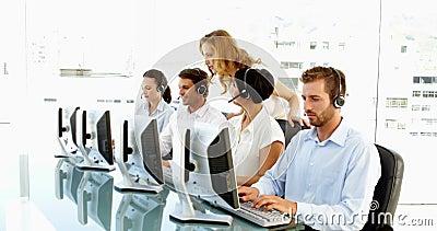 Supervisore che verifica gli impiegati di call-center video d archivio