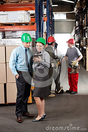 Supervisors With Digital Tablet Working At