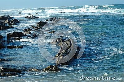 Surf along rocky coastline