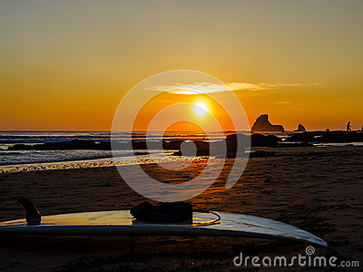 Surfboard on the rocky beach at sunset