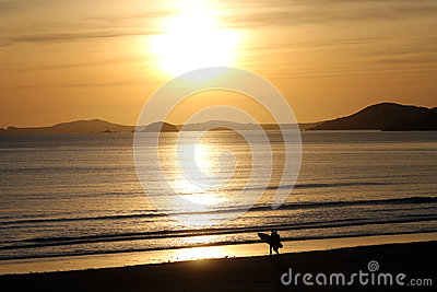 Surfer on Beach with Sunset Behind