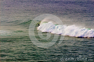 Surfer in rainbow wave