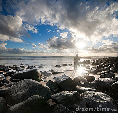 Surfer on rocky beach at striking light