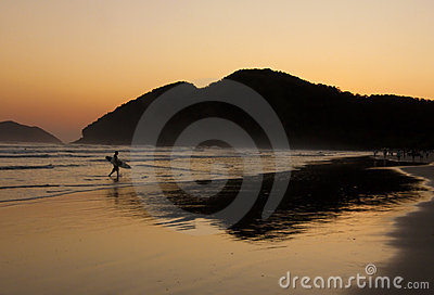 Surfer and Sunset Reflexion in the ocean