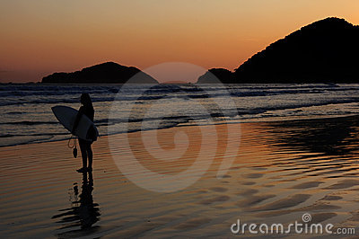 Surfer and Sunset Reflexion at a tropical beach