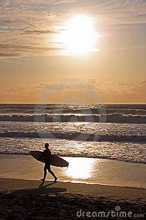 Surfer with surf board on beach, Fistral Bay, UK
