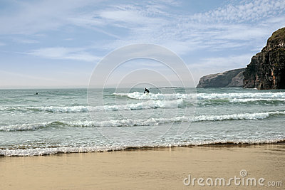 Surfer surfing near ballybunion cliffs