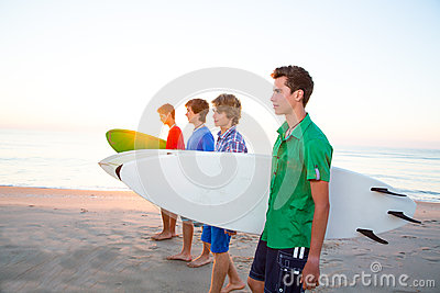 Surfer teenager boys walking at beach shore