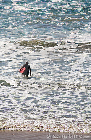 Surfer wading into sea with surfboard