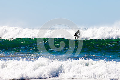 Surfer in wetsuit surfing breaking waves off beach