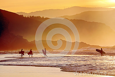 Surfers and boogie boards at sunset
