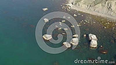 Surfeur de soupe nageant entre les rochers qui s'élèvent dans l'eau. Bande côtière rocheuse étroite clips vidéos