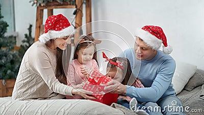 Surpreendente família feliz em roupas festivas abrindo caixa de presentes juntos celebrando o Natal video estoque