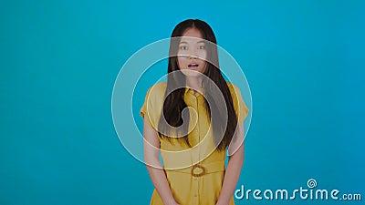 Surprise face excitée d'une femme asiatique surprise isolée sur fond bleu Jeune fille asiatique en t-shirt d'été Espace de copie banque de vidéos