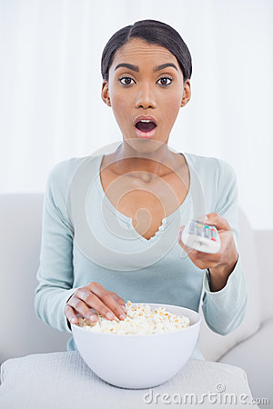 Surprised attractive woman eating popcorn while watching tv