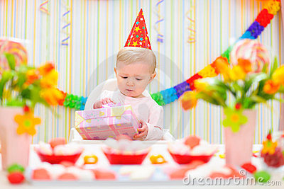 Surprised baby looking on gift on first birthday