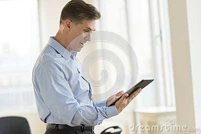 Surprised Businessman Using Digital Tablet In Office