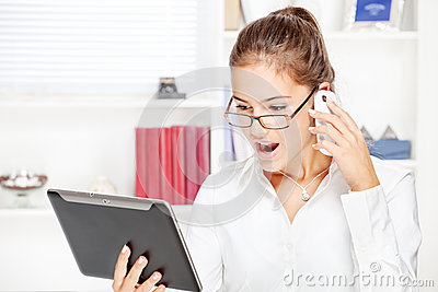 Surprised businesswoman looking at tablet computer