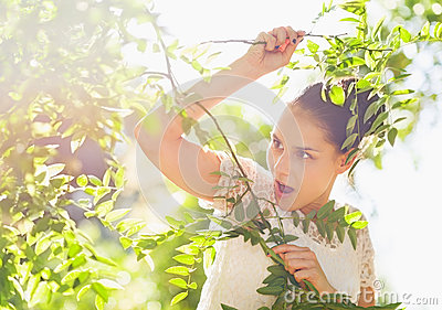 Surprised girl in foliage looking on copy space