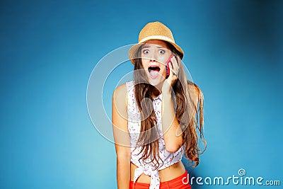 Surprised girl talking on mobile phone