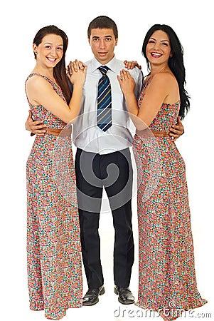 Surprised man holding two laughing women