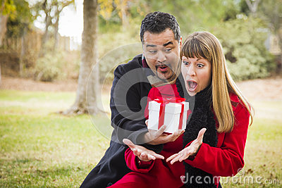 Surprised Mixed Race Couple Giving Gifts