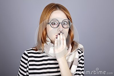 Surprised red-haired girl in glasses and scarf.